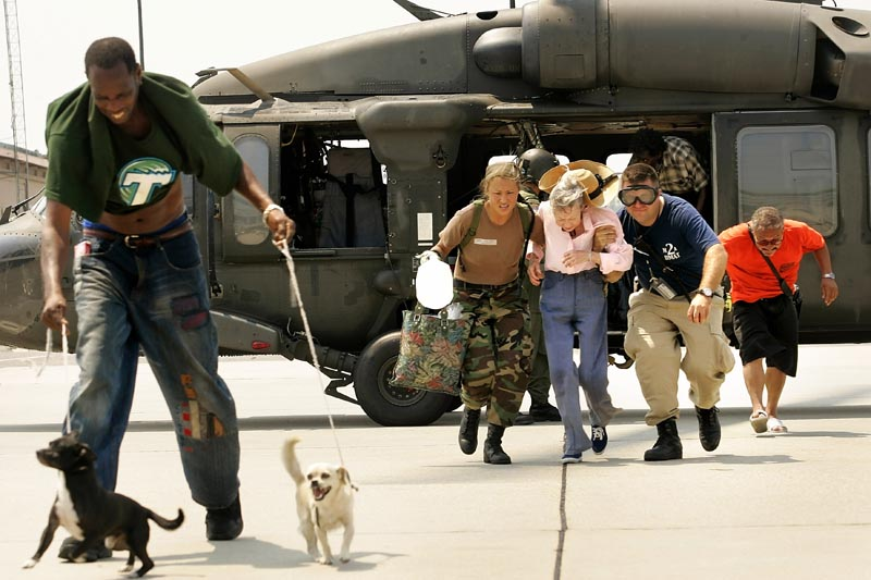 Teams worked in the blazing sun to evacuate refugees from Hurricane Katrina, who were arriving ath the Louis Armstrong New Orleans Airport on Saturday afternoon, September 3, 2005.