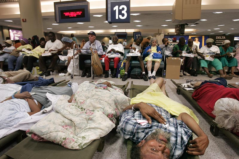 These gravelyill evacuees awaited further aid by the baggage  claim carousels. Some patients were stabilized and given there medications, but the medical personel were overwhelmed by the volume. Next to one of the patient dispatch areas (which was fomerly a traveler lounge area as part of the airport) was a temporary morgue, where one medical worker said that personel would take DNA samples from the bodies before embalming them and placing them in refrigerated trucks on the premises.
