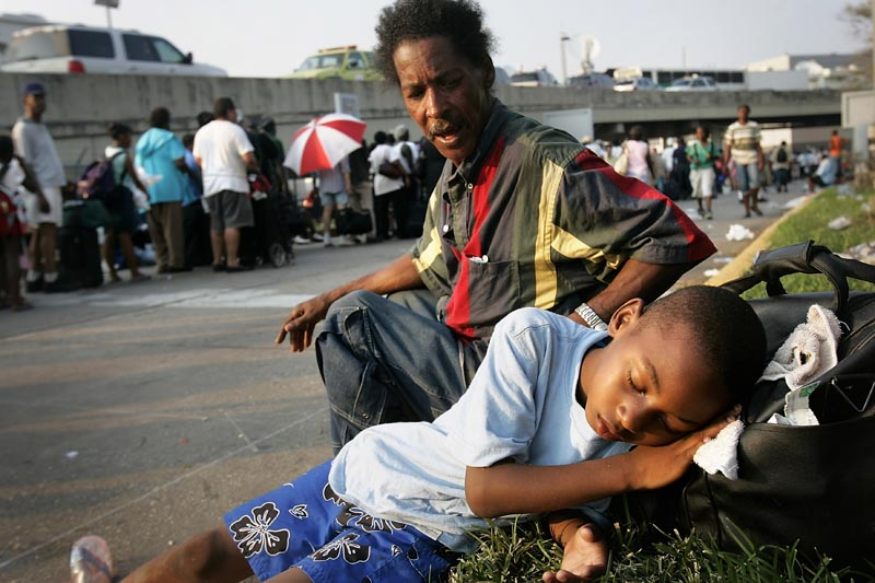 Michael McMillan, 8, cq, lay listless and unresponsive to his uncle Arthur Beasley's attempts to rouse him as they waited in the hot sun to be admitted to the New Orleans airport. Michael was severely dehydrated and needed medical attention.
