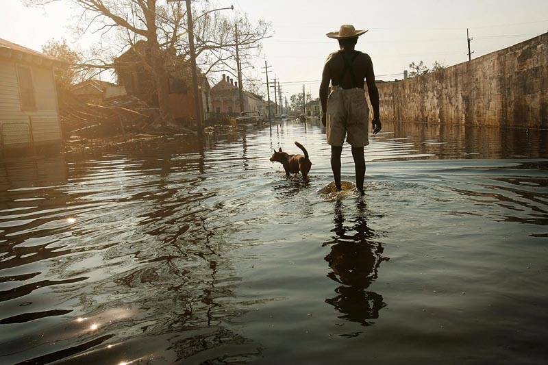 NEW ORLEANS, LOUISIANA -- 9TH WARD.  Paul Garrett, 56, and his neighbor's dog, Rusty, whom he rescued during Hurricane Kartina, walk the streets of the 9th ward on their way home. {quote}Everybody left,{quote} said Garrett, a former longshoreman. {quote}I stayed.{quote} Garrett said he stayed to help the neighborhood's elderly and sick. {quote}Everybody can't leave,{quote} he said. {quote}I'm lookin' [sic] out for people who can't help themselves. Especially the older people. See, I'm just a 'junior citizen.' They're 'senior citizens',{quote} he continued. {quote}You got a lot of people in this city who don't care for each other. I feel like we should pull together now instead of apart. It's gotten worse. It's not right,{quote} he said.