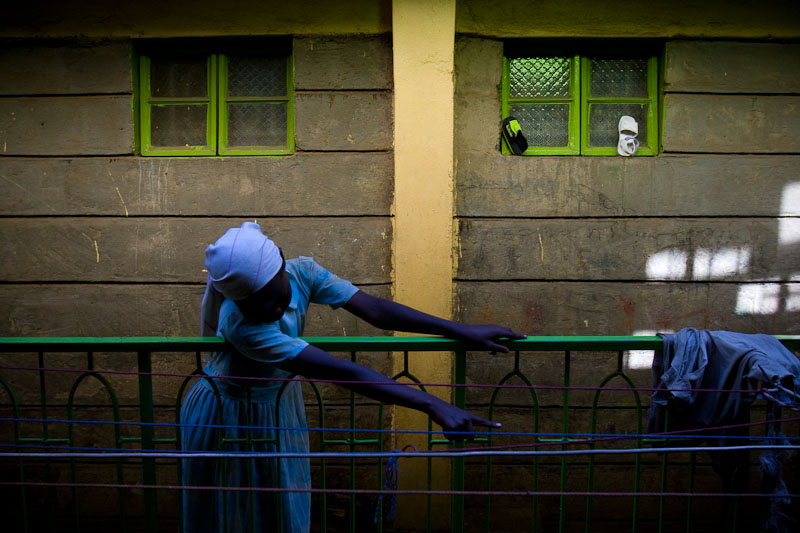 A young girl talks to a friend several floors below hers in a sprawling, leaky and unsafe apartment building in Kenya's slums. Individual housing units frame an open and unguarded stairwell over which residents hang laundry to dry.