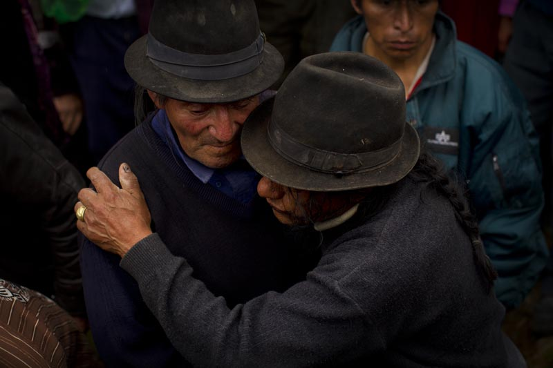 The father and grandfather of the murder victims, Felix Palaguachi, hugged a relative during the burial of his daughter and grandson. Like many men in the town, he was heavily intoxicated for the entire the weekend of her wake and funeral.