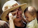1/25/2005 -- Banda Aceh, Indonesia -- Mohammad Budi Permana breaks down while holding a baby girl who is from his village. Permana lost his fifteen-month-old daughter, Anya, in the tsunami and has not yet given up hope of finding her, alive or dead. He asked to hold the child (Edi Mulfi) to test himself, he says. {quote}I though I could be the strong man,{quote} he later said. While he was holding Mulfi, he cried out {quote}I remember my daughter!{quote} and burst into tears. He said he previously managed to keep his emotions under control and his mind occupied in his search, but when he held the child, he lost control. He cried for a long time (20 minutes in the car); when he was composed, he brushed an eyelash that had fallen onto his left cheek, remarking, {quote}In Indonesia, when an eyelash falls, it means someone misses you.{quote} He added, {quote}If [it falls on the] left, it means she is far...if it falls on the right, it means she is close.{quote} He concluded, {quote}That means my child is alive. Somewhere.{quote}  Photo by Dina Rudick, Globe Staff              Could accompany story about reuniting children and parents through DNA testing, emotional fallout and psychological issues.