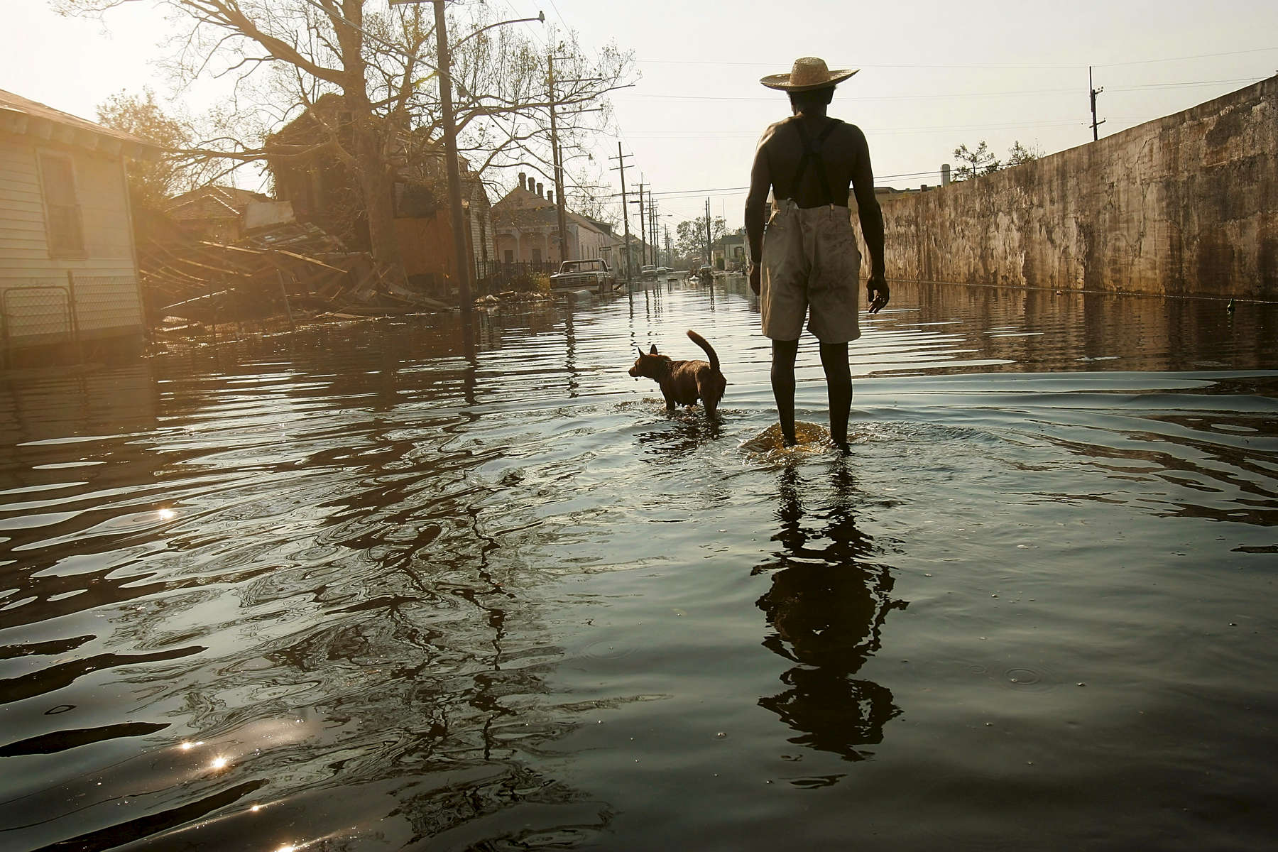 9/4/05 -- New Orleans, Louisiana -- 9th Ward -- Paul Garrett, 56, and his neighbor's dog, Rusty, whom he rescued during Hurricane Kartina, walk the streets of the 9th ward on their way home. {quote}Everybody left,{quote} said Garrett, a former longshoreman. {quote}I stayed.{quote} Garrett said he stayed to help the neighborhood's elderly and sick. {quote}Everybody can't leave,{quote} he said. {quote}I'm lookin' [sic] out for people who can't help themselves. Especially the older people. See, I'm just a 'junior citizen.' They're 'senior citizens',{quote} he continued. {quote}You got a lot of people in this city who don't care for each other. I feel like we should pull together now instead of apart. It's gotten worse. It's not right,{quote} he said. Photo by Dina Rudick, Globe Staff.