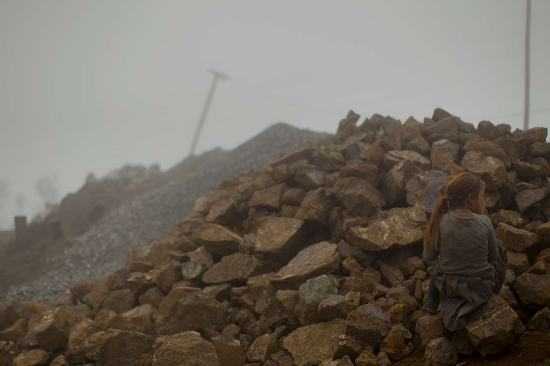 2/26/11 - Cañar Province; Ecuador - A young girl blends into a pile of rocks next to her home, high in the Andes in an isolated pocket of Ecuador. This is a scene setter near the home of Murder suspect Luis Guaman's estranged wife. Guaman is now in an Ecuadoran prison charges of forgery and using a false passport. He left behind four sons when he immigrated to the United States to work. He is the primary suspect in the bludgeoning deaths of Maria Avelina Palaguachi-Cela and her 2-year-old son, Brian. Story by Maria Sacchetti/Globe Staff. Dina Rudick/Globe Staff.