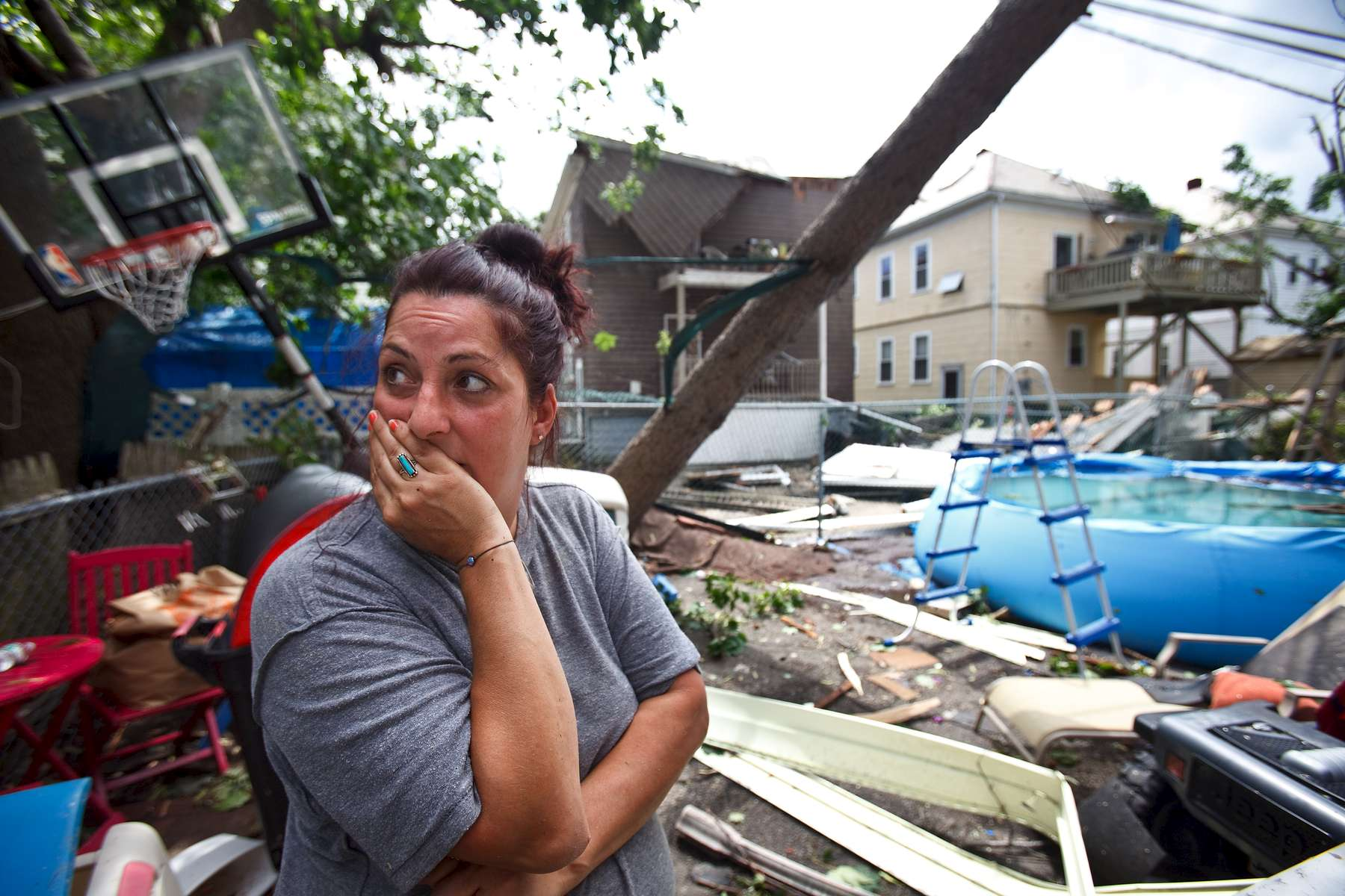 7/28/14 - Revere, MA - Barbara Cardone, cq, surveys the damage done to her formerly orderly back yard on Taft Street. A tornado ripped through Revere, MA on Monday morning, July 28, 2014. Item: 29weather. Dina Rudick/Globe Staff
