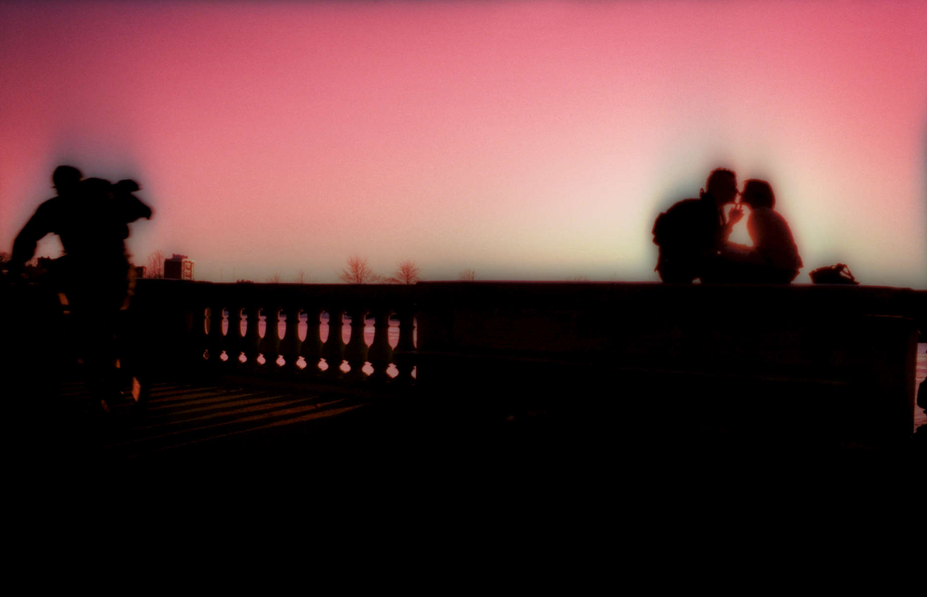 3/22/2005 -- Boston, MA -- The Esplanade -- Lovers kiss at sunset on the Esplanade in Boston, MA on Tuesday evening, March 22, 2005. For Magazine back cover. Photo by Dina Rudick, Boston Globe Staff. DO NOT ALTER THE COLORS OF THIS PHOTOGRAPH IN PRODUCTION!! IT IS SHOT ON CHROME FILM AND WAS CROSS-PROCESSED...THEREFORE THE INTENSE COLOR SHIFT AND SATURATION.