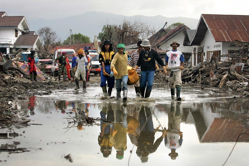 Bodies were still being discovered by the thousands each day in Banda Aceh, even a month after the December 26 tsunami. These workers haul a particularly heavy body through a puddle toward the body truck - an open-bed truck that hauled away dozens of bodies from the devastated zones.