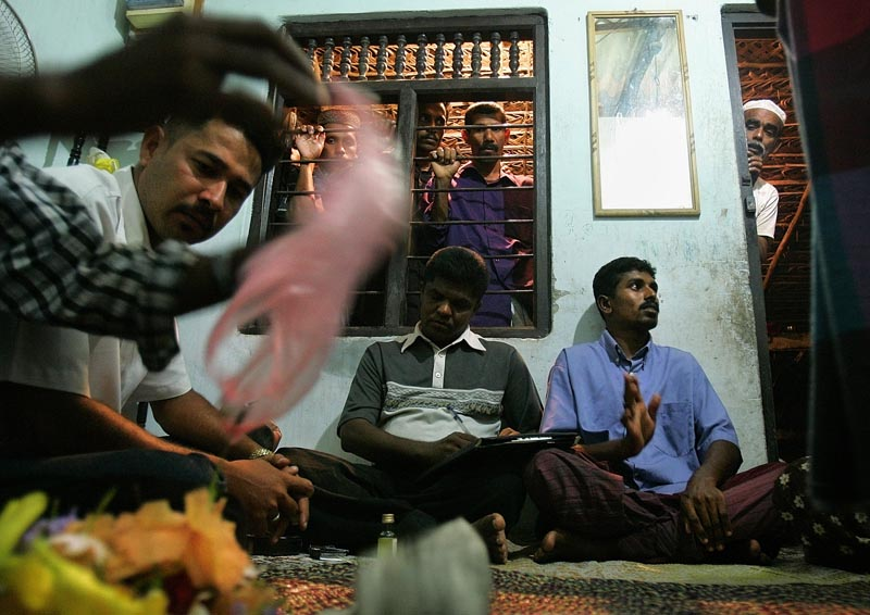 The traditional healer (in green shirt), Latif, held a midnight exorcism ceremony to rid AA Fawsor of the demons he said possessed him, which he attributed to contact with a menstruating woman.  He demanded very specific items for the ceremony including a variety of flowers in specific numbers, special kinds of roots and earth, spices, perfumed oils, tin foil, and various kinds of curry and meats.