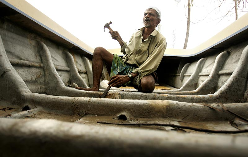 This Sri Lankan fisherman recovered his badly damaged boat and made slow progress to repair it.