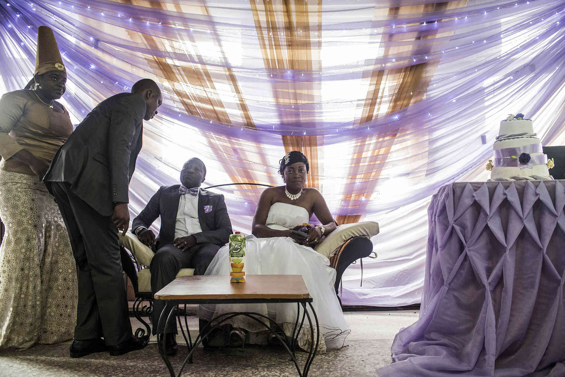 Groom Shadrach Uchenna, a wedding photographer, and his bride Ekpo Peace Emem sit at the front of a banquet hall during the wedding as guests greet them in Lagos, Nigeria.