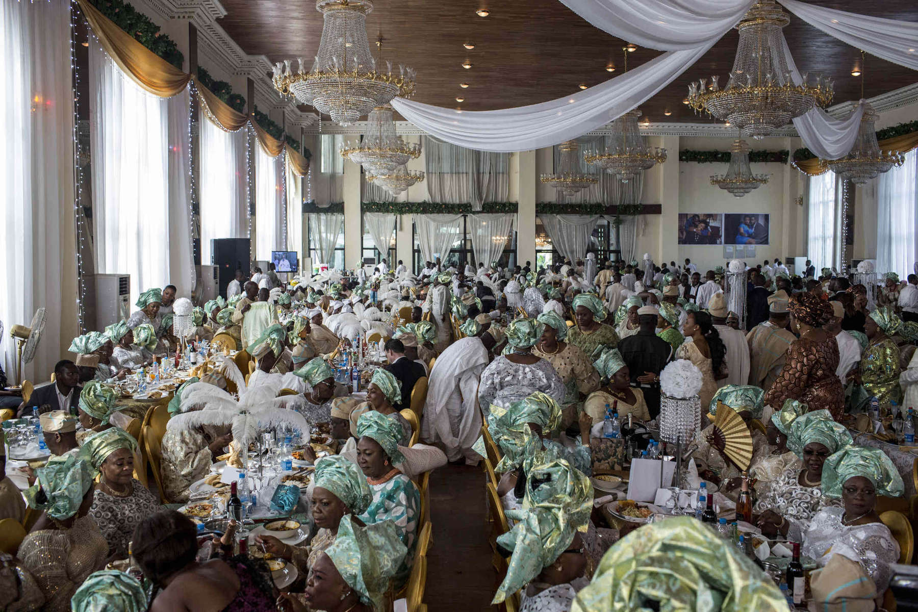 An opulent wedding for nearly a thousand guests was held at the banquet hall of a private housing estate in Lagos, Nigeria. Guests wear matching outfits and hats chosen by the bride's family.