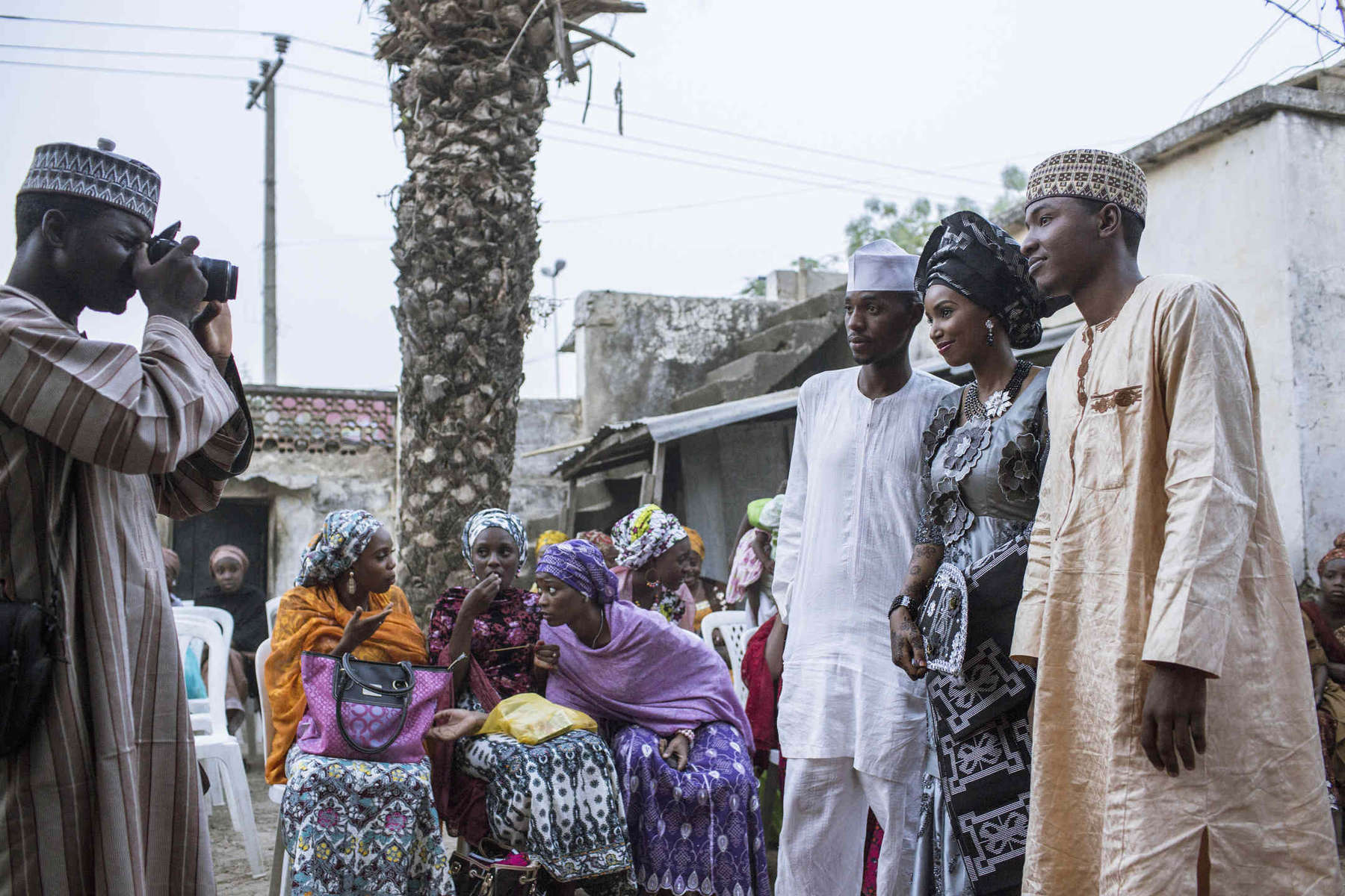 A wedding photographer snaps a northern bride with her husband and brother at a ceremony in Kano, Nigeria.