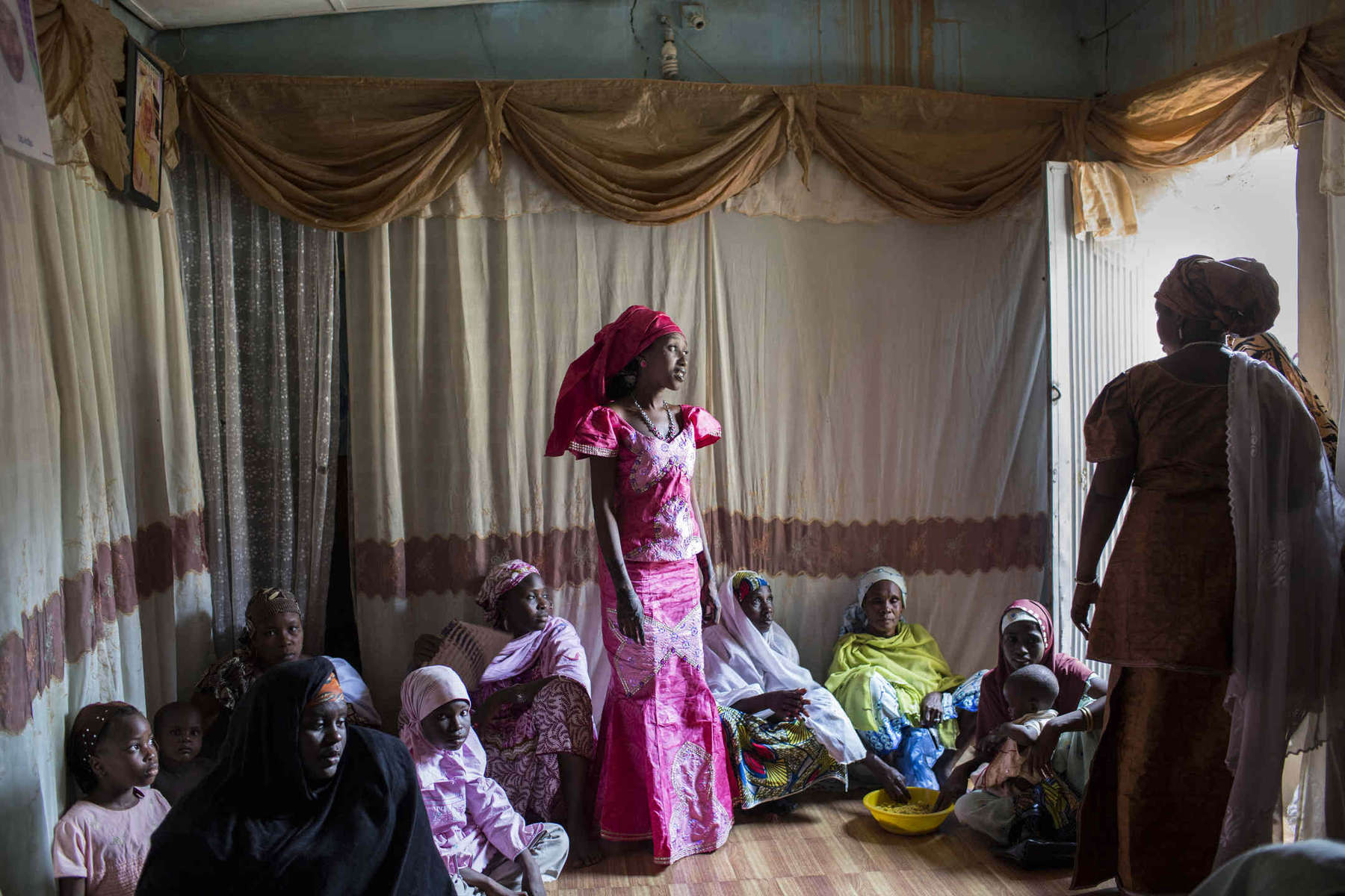 A young girl, who says she's 18, prepares to be the second wife of a civil servant during the women's part of her wedding ceremony in conservative Muslim Northern Nigeria.