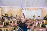 A hostess at a large high and high end wedding in Lagos wears a dress tailored from the same fabric that is used to decorate the chairs.