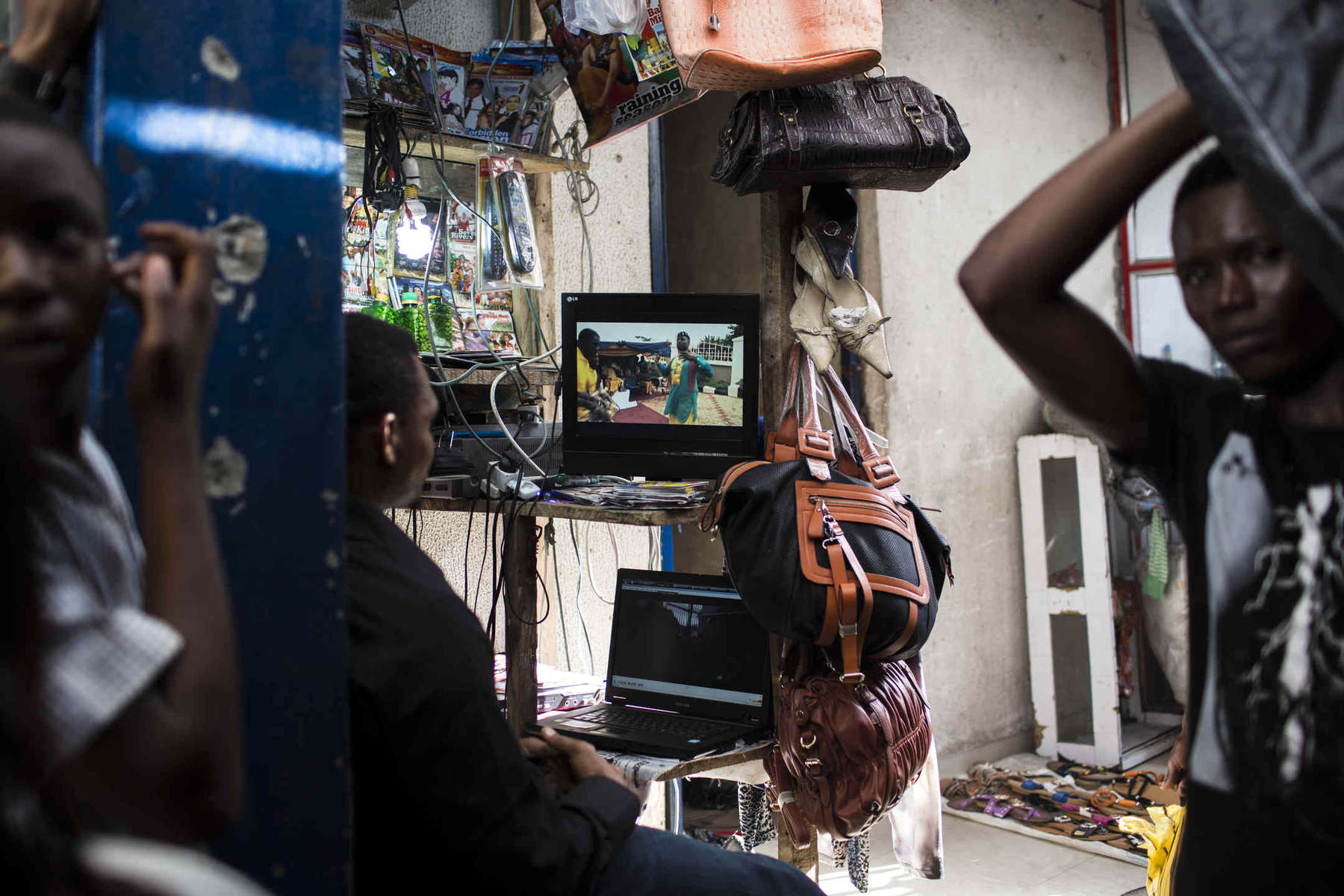 At a market in Lekki, Lagos, a man watches a Nollywood movie as porters bustle around and business is conducted on May 26.