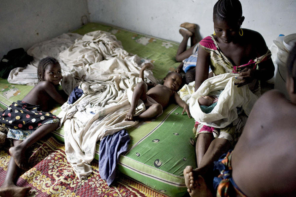 A family of Ivorian refugees in Liberia moves into a small one room house at a site that was used for internally displaced people during Liberia's civil war. February, 2011.
