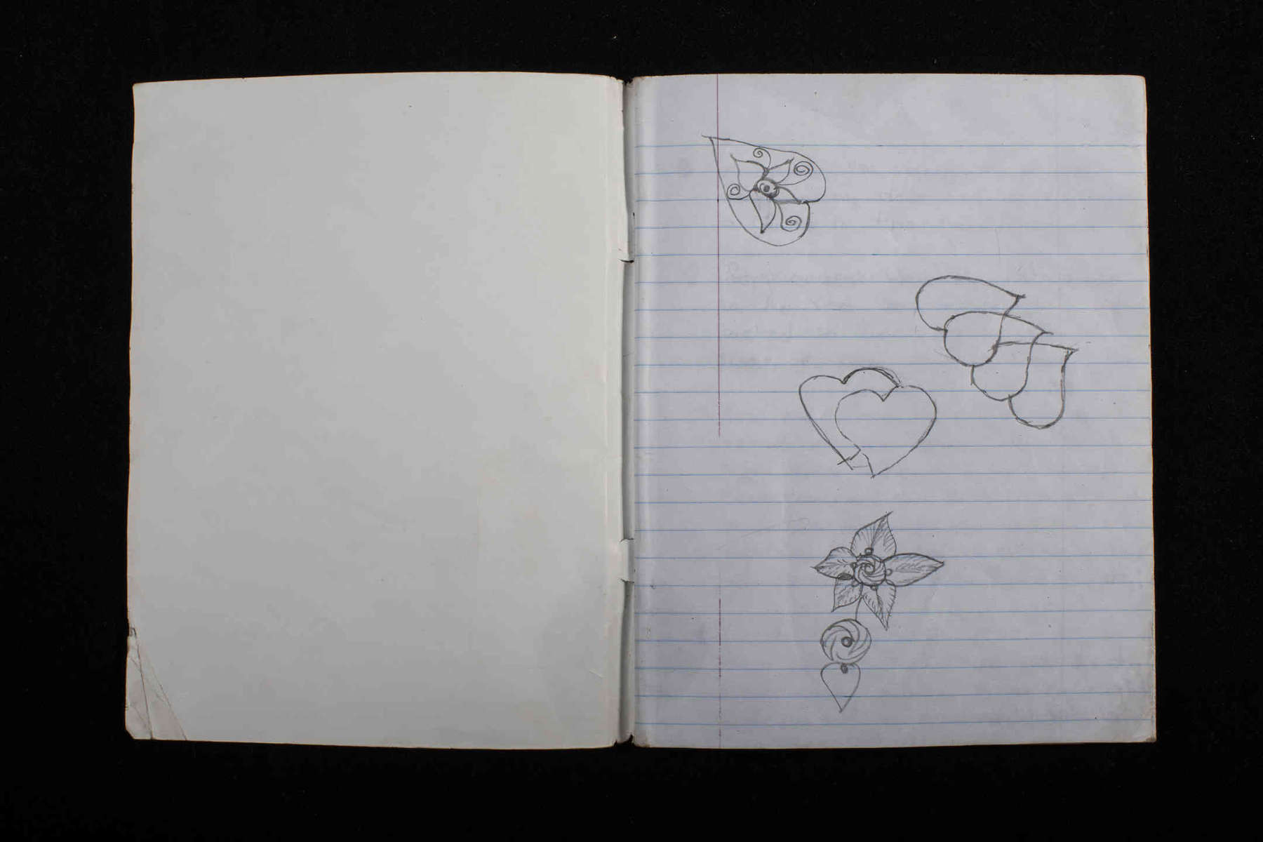 Dorcas draws hearts on the first page of her notebook.