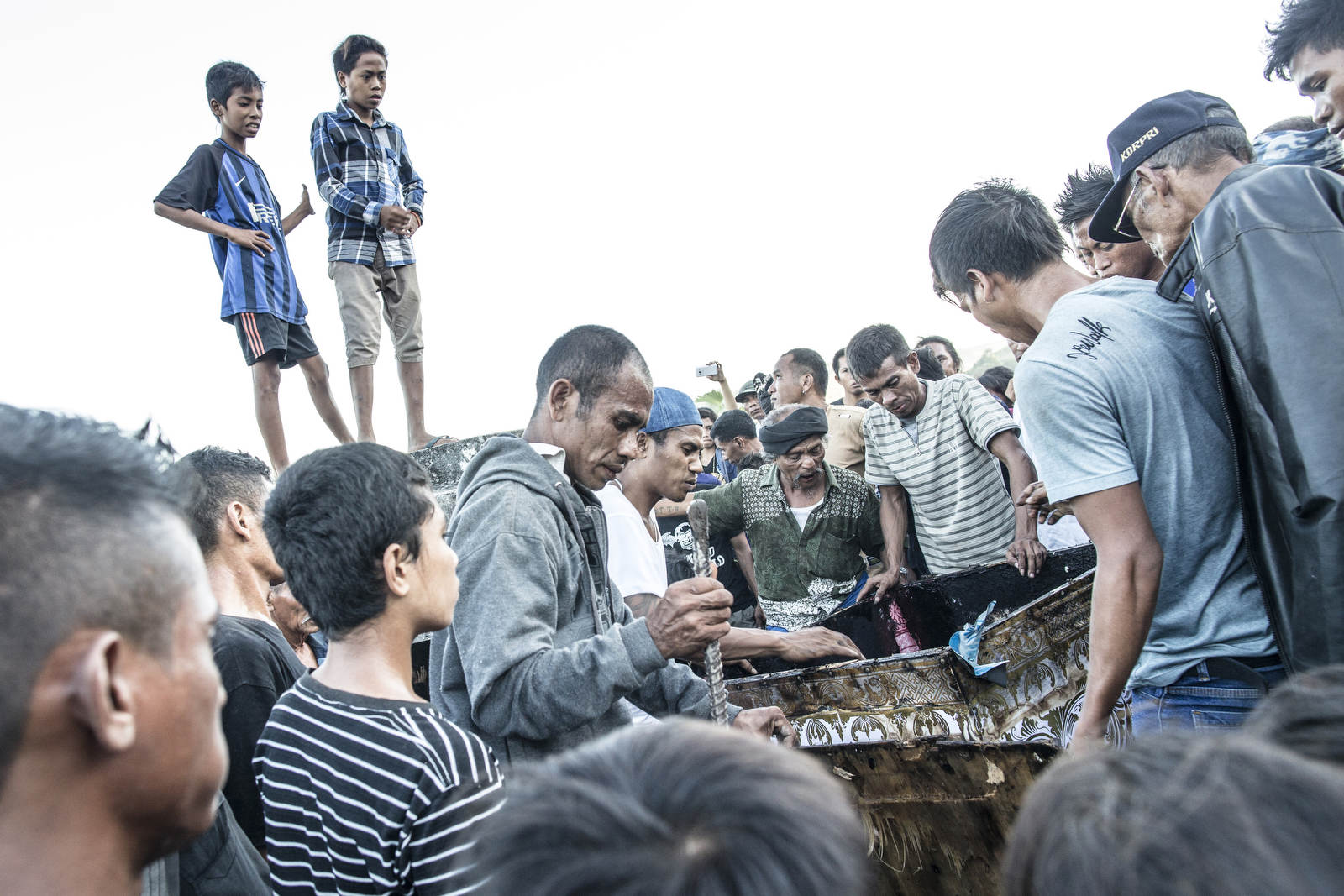 Young boys look on as the box in which the deceased is opened. After more than a year of sitting in the living room, the body has decayed beyond recognition. The practice of keeping the body in the house allows for a slow and less painful goodbye.