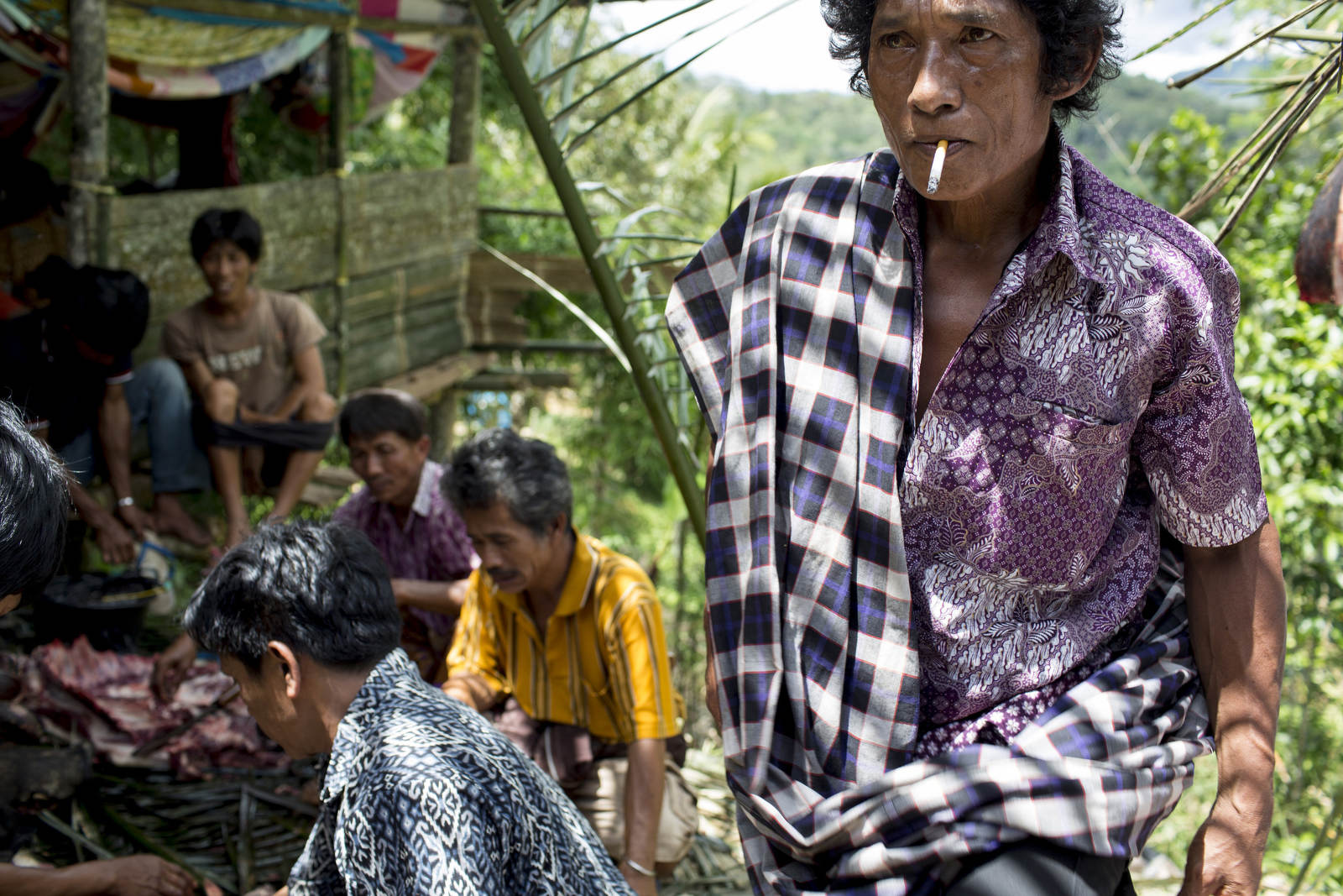 A man takes a smoke break at a funeral after helping butcher and divide the animal sacrifice offerings into portions for the guests.