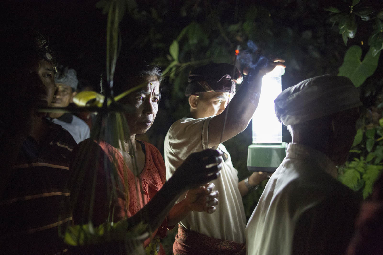 A woman says a prayer at ceremony at midnight by the banks of a river as part of the funeral procession for a high priestess in Gianyar, a part of central Bali.