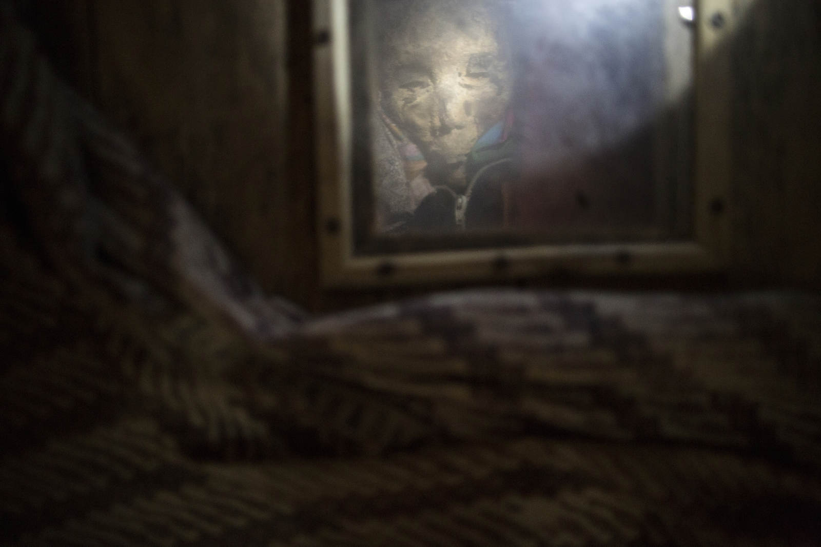 Maria Deten, who died in May 2011, in a coffin with a opaque window, in her home in Toraja, Indonesia. Her family will keep her body around as they save money for an elaborate funeral procession. This also gives relatives time to say their goodbyes.