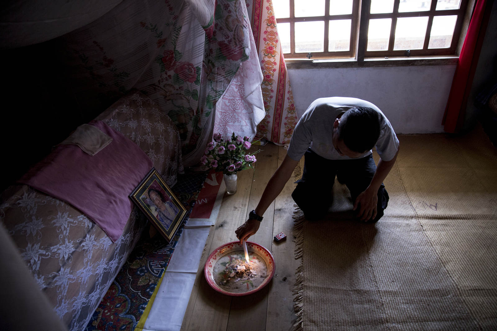 Fyant lights a candle for his grandmother, who has been dead since 2009. His family is saving up money for her funeral.