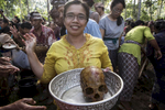 A woman holds up the skull of her relative in KlungKlung, a village in Bali. In this area, relatives are all buried in a graveyard, and then every three to five years, there is a ceremony where their bodies are exhumed, the bones are washed, then cremated, and then the remains are thrown to the sea. The mood was festive as hundreds of people fathered for the ceremony.