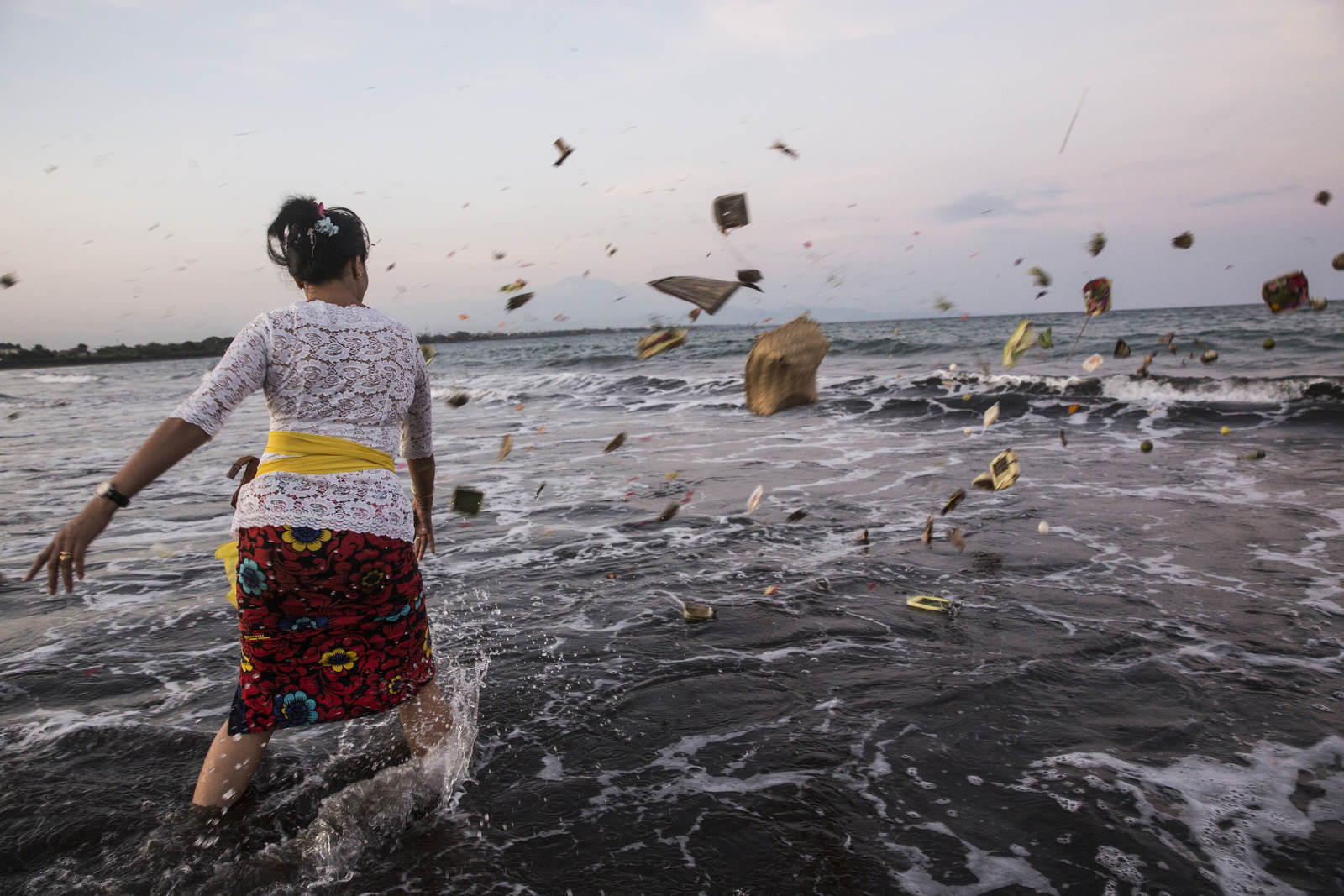 A woman throws offerings to the sea for her deceased relative in Bali, Indonesia.