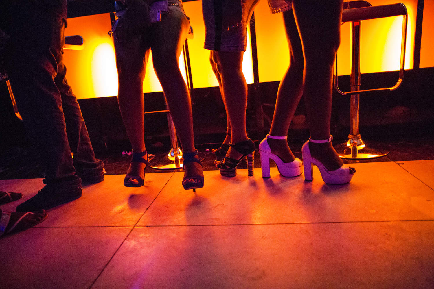 Girls stand by the bar, all dressed up, at 57, a high end night club in Lagos, Nigeria.