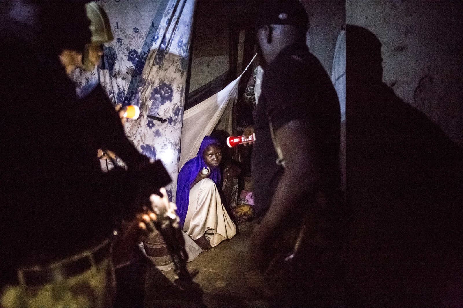 A young woman looks up at a solider who is checking her house for insurgents, weapons or other illicit goods during a cordon and search exercise after a suicide bombing on the outskirts of Maiduguri.