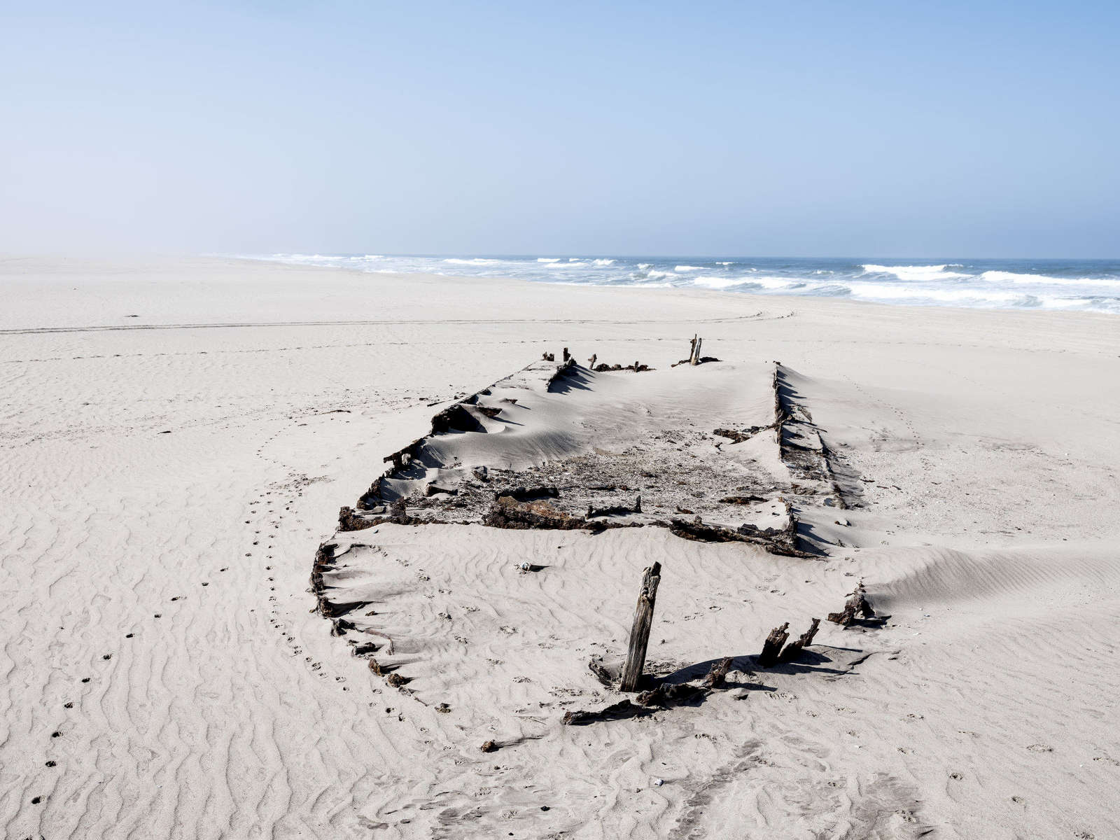 Unknown boat. The harsh climate has destroyed most of it, but the parts under the sand remain as testament to the crash. It is likely often completely covered and invisible. S21°13'43.4E013°39'41.8