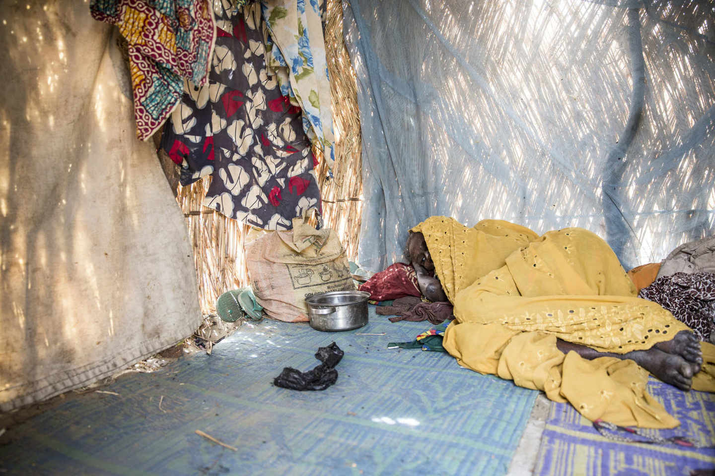 Inside of a thatch hut, a woman rests and tries to eat small bits of rice in a makeshift refugee camp in Monguno, an area of Borno state that was previously held by Boko Haram but has been newly liberated by the Nigerian Army.