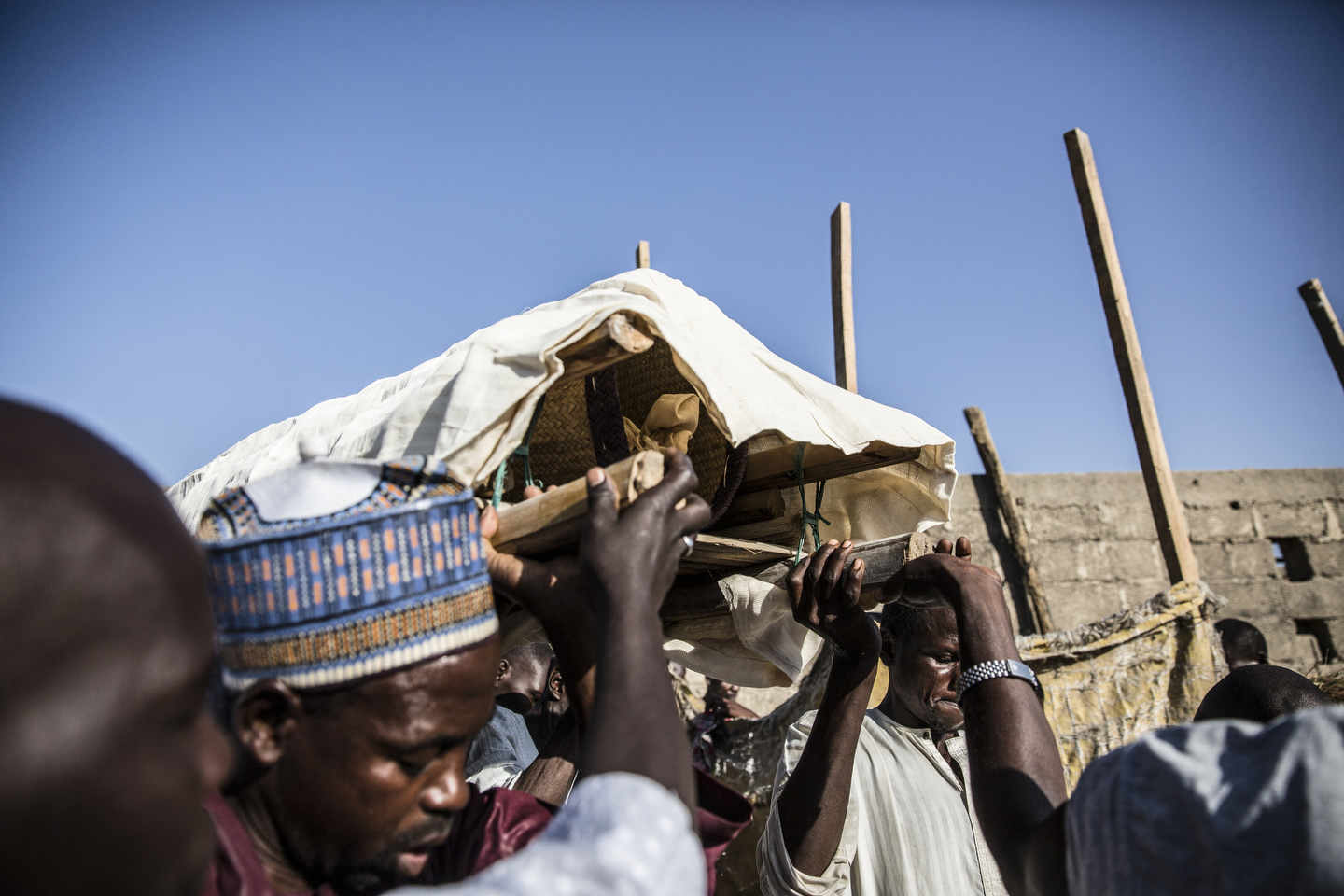 Men prepare the bodies for burial after a suicide bomb in Nigeria.