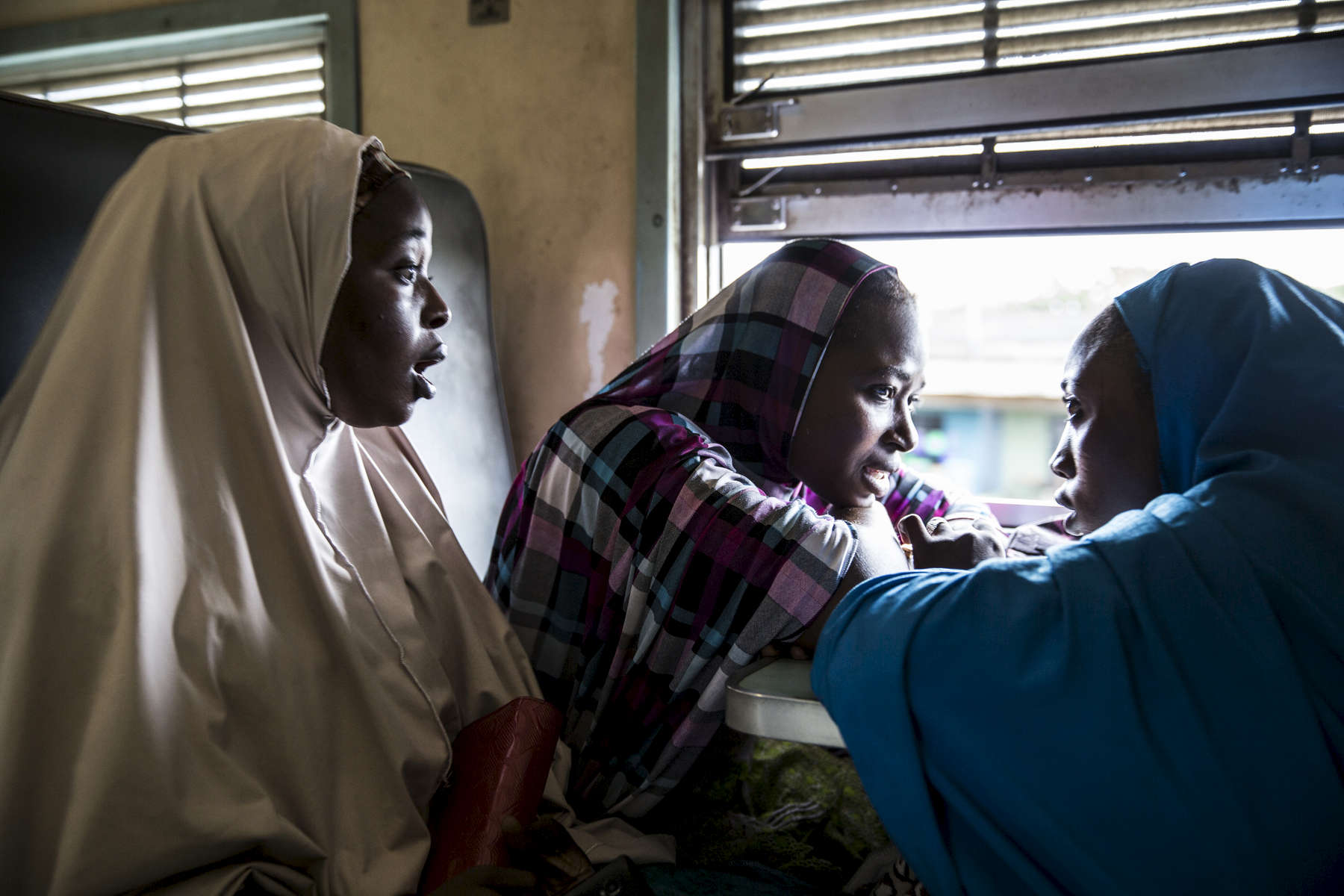 Sumawya Ibrahim, in the blue hijab, travels with her two sisters by train from Lagos to Zaria. They prepared for the journey for two days, making rice and beans to bring with them. Only one of the three girls is married and the other two hope to marry soon.No phone number.