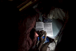 A woman reads a Hausa romance novel using the flashlight on her cell phone as the train chugged along slowly through the night.