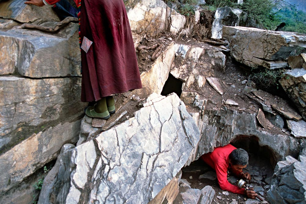 Tibetan pilgrims enter and exit a 'Bardo' hole whilst on pilgrimage in practise for the enxt life.Yunnan Province, China