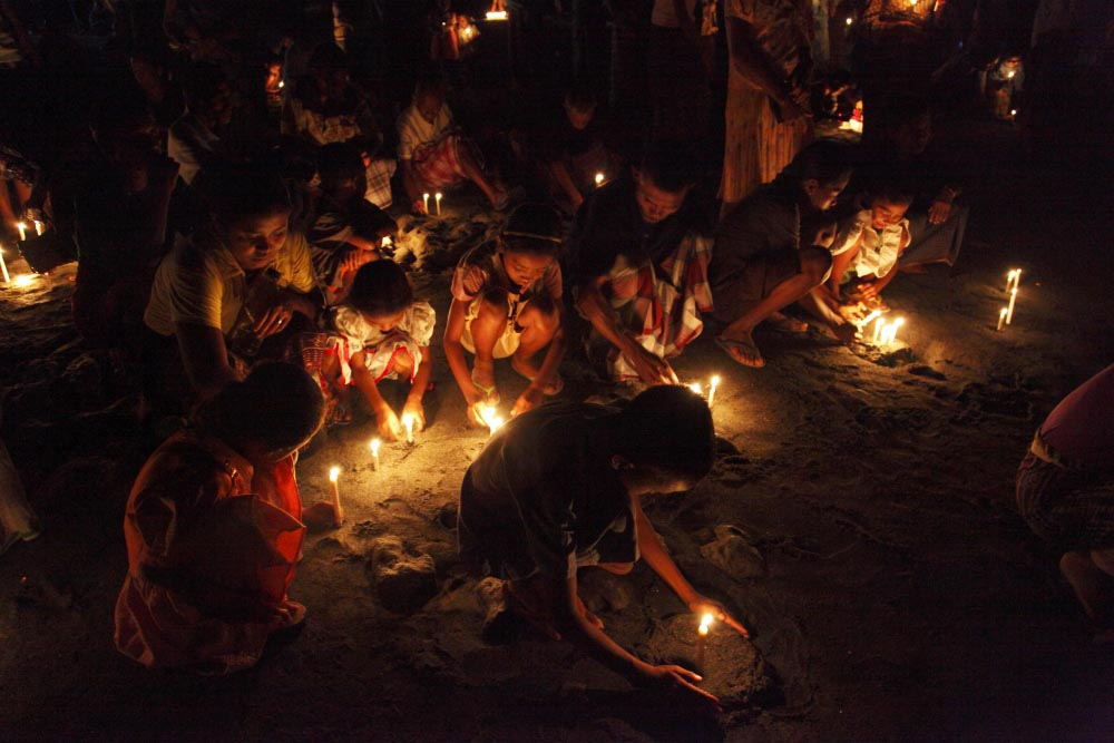 Familys light candles on the beach during the ceremony of 'misa arwah'. A remembrance service held once a year to pay respects to those who died at sea during a hunt, numbering 36 since 1917.Lembata Island, Indonesia