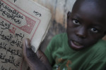 A almudu or student sits behind a sheet of Arabic text at the dara or religious school in the Gambian village of Daru Relwan. (THE INDEPENDENT/Simon Akam)