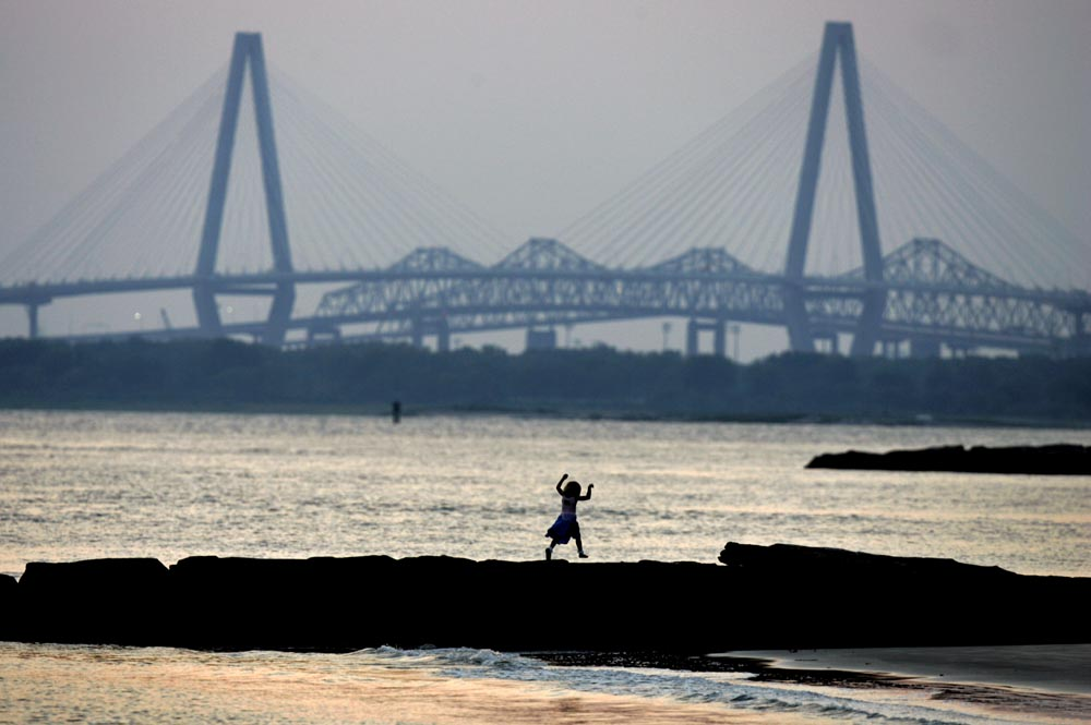 While working for The Post and Courier in Charleston, Mic Smith helped chronicle the construction of a new Cooper River Bridge from Charleston to Mount Pleasant.  This image shows a unique point in time when the new bridge was almost finished but the two older bridges had yet to be dismantled. It also is a favorite of Mic's, because the image of the girl running across the rocks along Sullivan's Island represents the simple joy of childhood and all its possibilities.  All Photos/Mic Smith Photography LLC