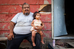 George Eagle Bull sits with his niece, Kimimilia, in front of his house in Pine Ridge, South Dakota, on Friday, July 24, 2009.