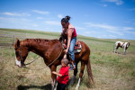 A young mother helps her son onto the horse on Pine Ridge Reservation, South Dakota.  Family values are something that elders in the community see as being lost among the younger generations as they turn to drugs, alcohol, and gang activity.