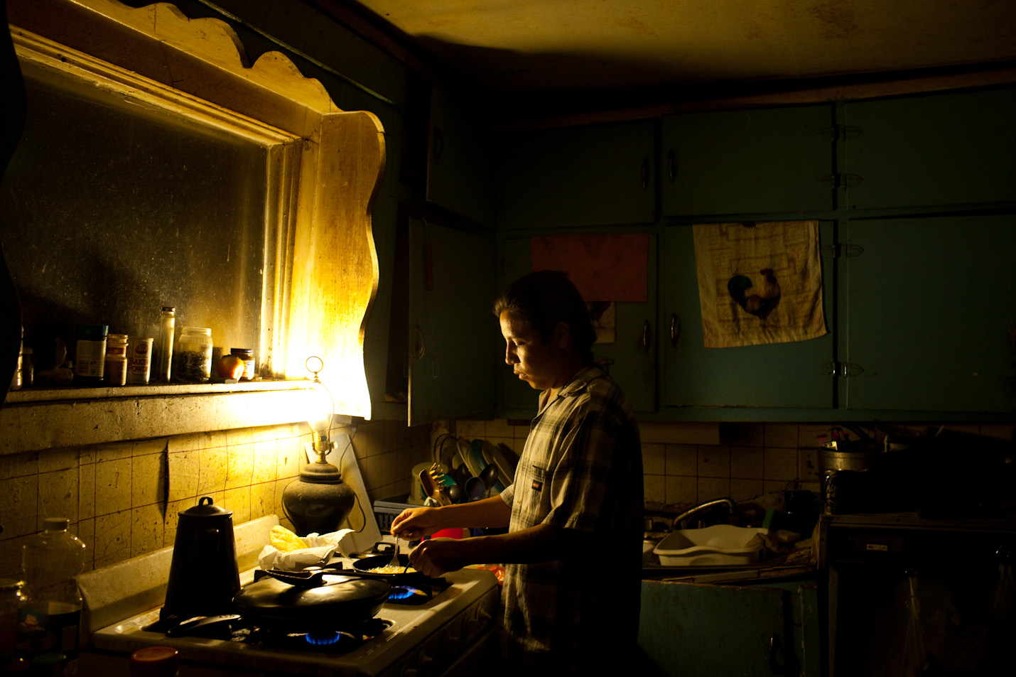 Rich Lone Elk, 24, cooks dinner at his house in Pine Ridge, South Dakota.  The house, which lacks basic amenities like plumbing is home to as many as 8 people.