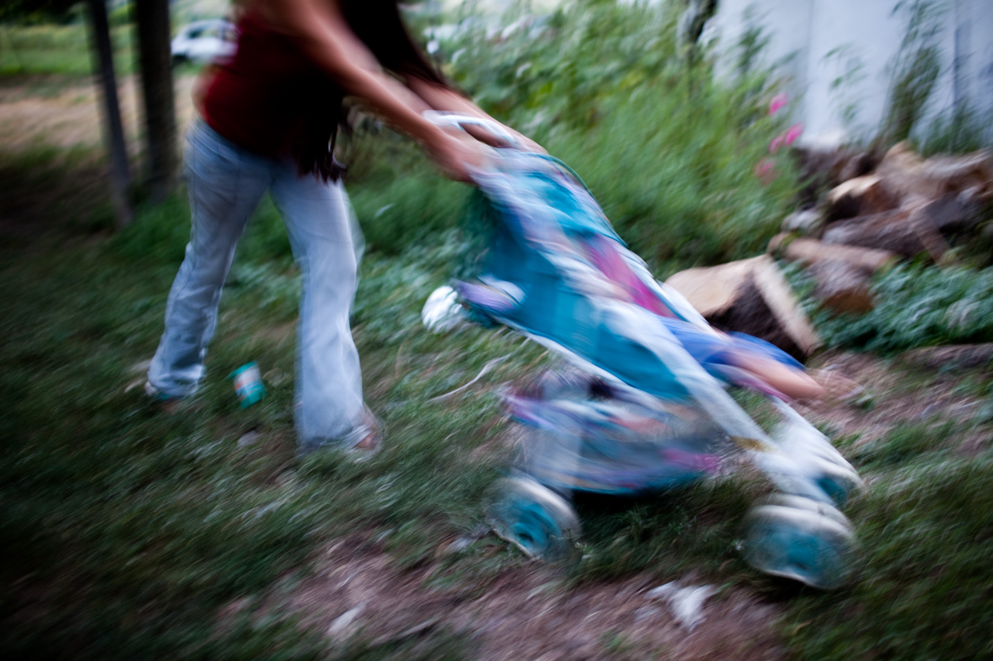 Alexis Oxendine pushes a stroller through the front yard in Pine Ridge, South Dakota.  Many houses lack basic amenities such as running water and electricity.