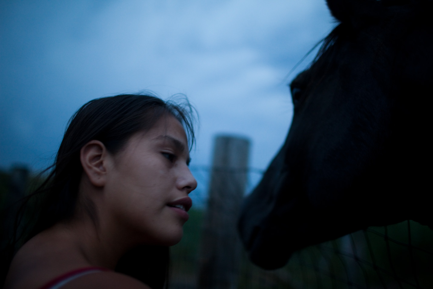 Alexis Oxendine pets one of the horses on Pine Ridge Reservation.  Many people use horses a primary means of transportation during the summer to get from place to place.