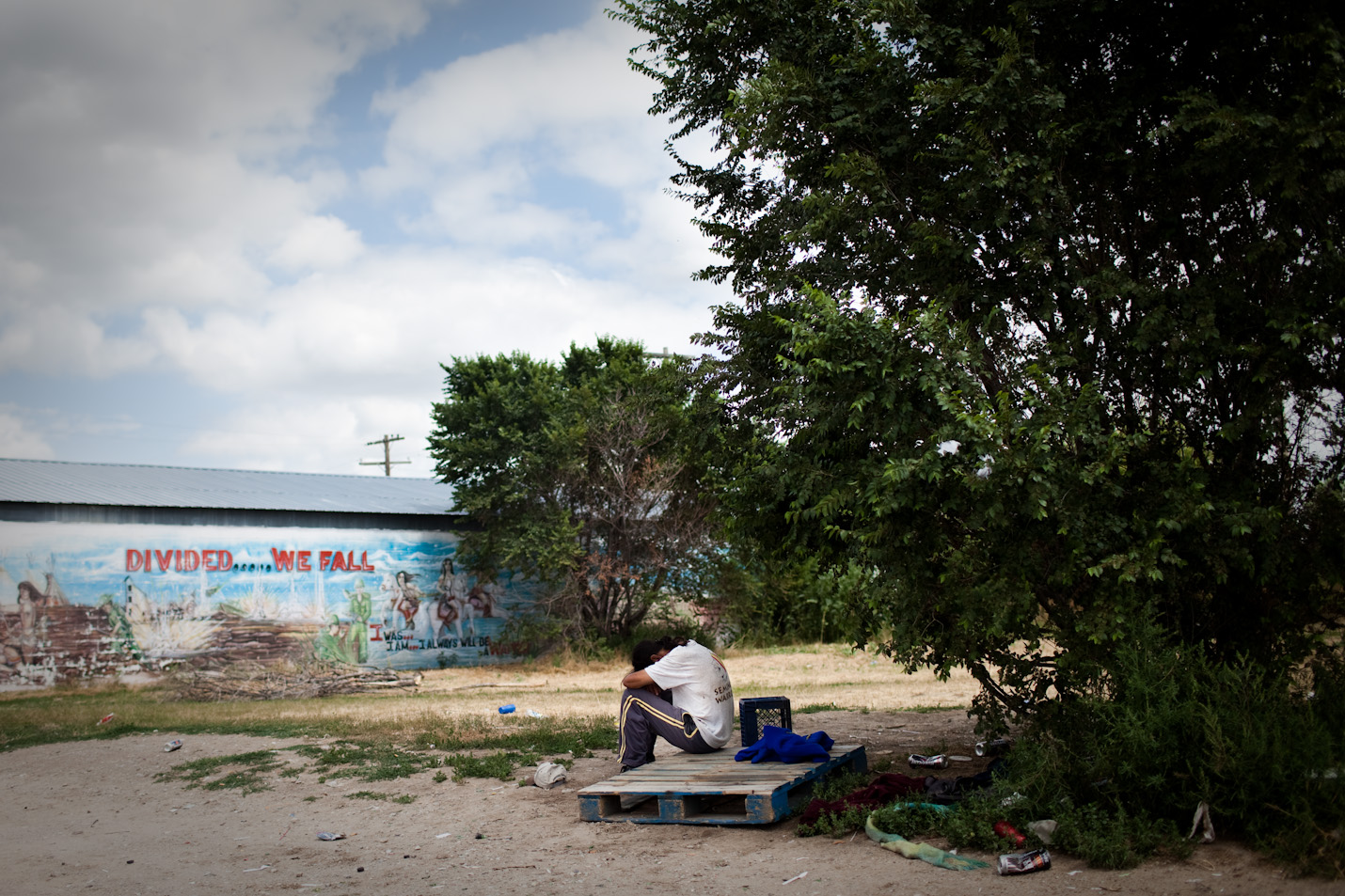 A man sits with his head in his hands in White Clay, Nebr.  White Clay, population 17, which is merely two miles away from Pine Ridge, consists of four liquor stores that sell an average of 12,500 cans of beer a day, mostly to the residents of Pine Ridge Reservation.
