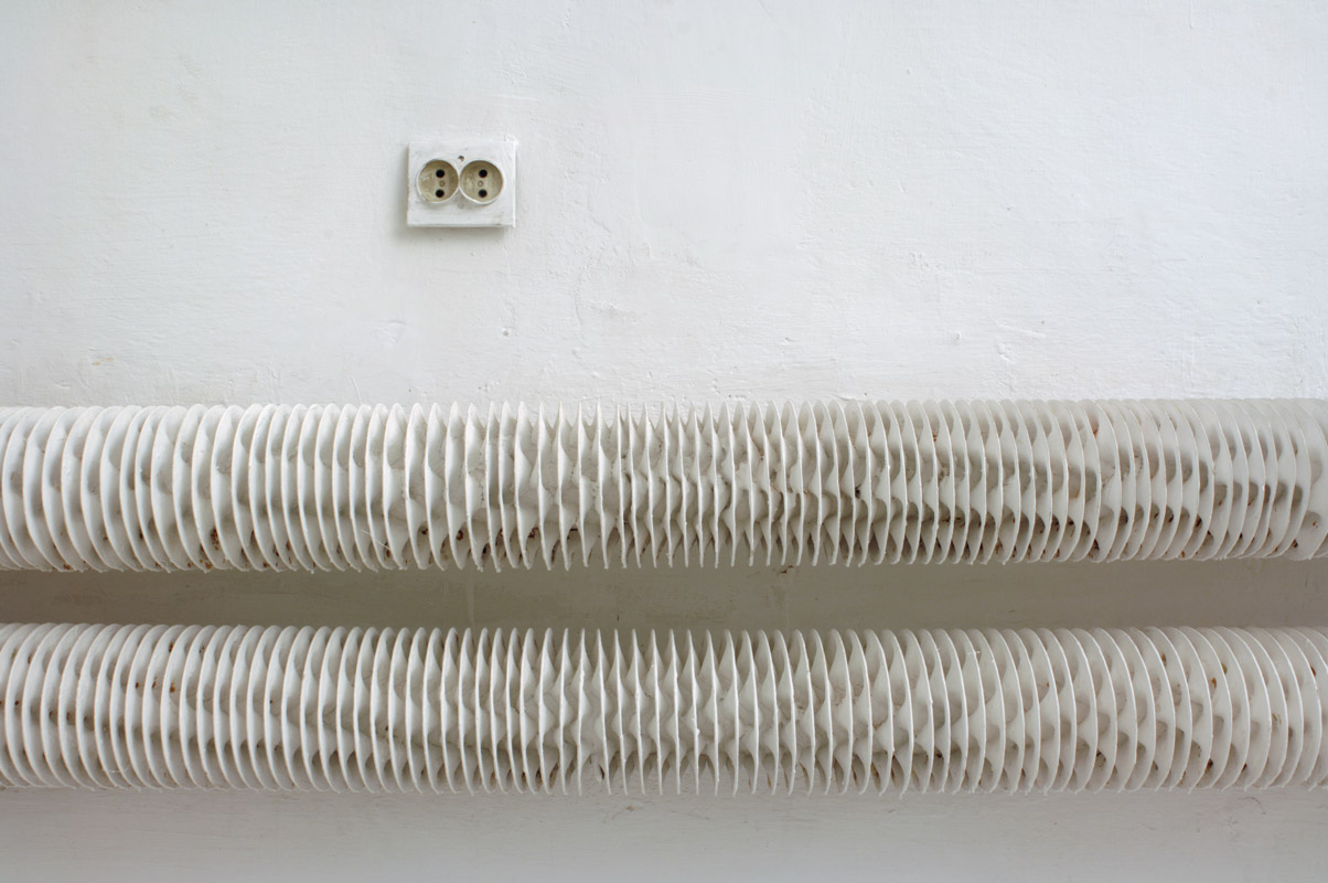 Abstract white composition with a wall socket and twirly object (radiator)