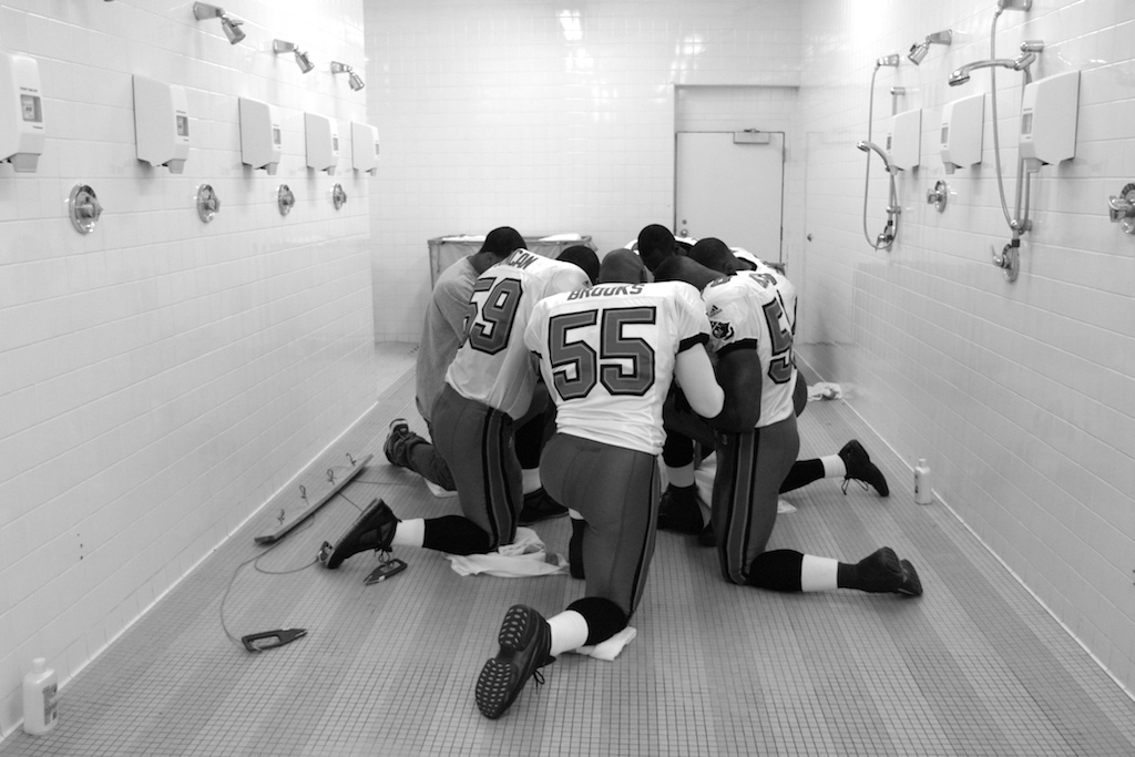 Members of the Tampa Bay Buccaneers huddle to say a prayer in the shower room of the visitors' locker room at the Pontiac Silverdome.