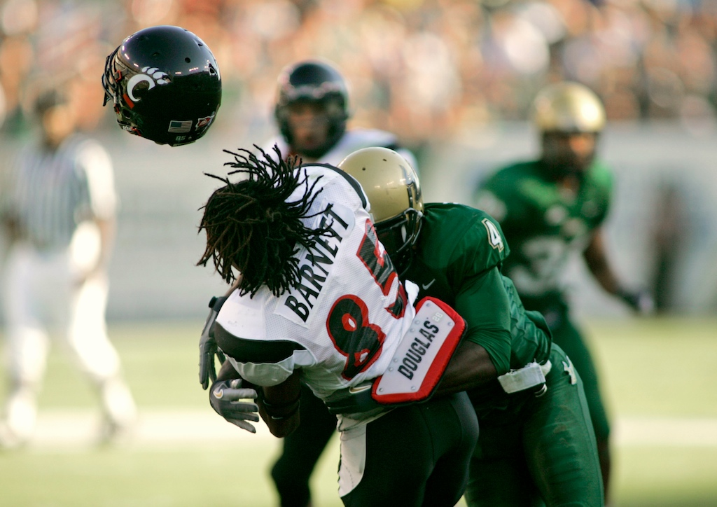 Cincinnati WR Marcus Barnett (85) gets his helmet knocked off by South Florida DB Mike Jenkins (4) during the first half of their game at Raymond James Stadium.