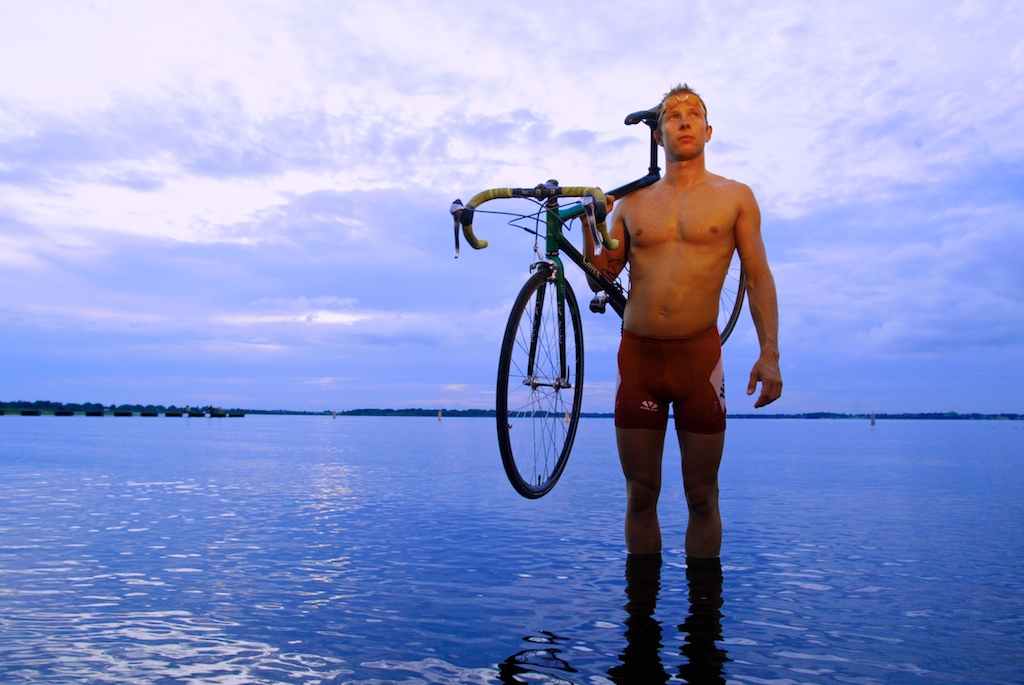 Triathlete Andre Fosta poses for a portrait with his bicycle while standing in Lake Minneola.